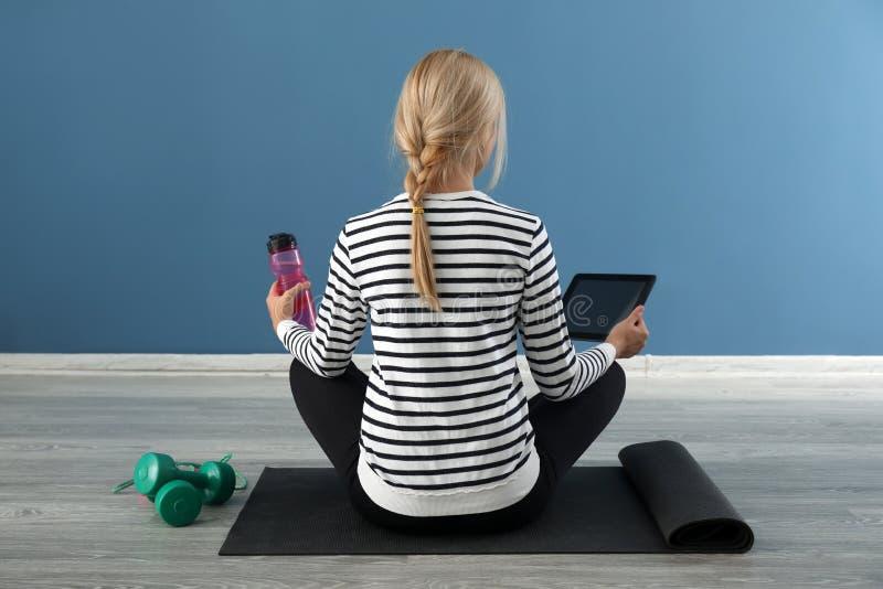 Junge Frau mit dem Tablet-PC und Flasche Wasser zuhause sitzend auf Yogamatte Konzept der Balance zwischen Rest und Arbeit stockfotografie