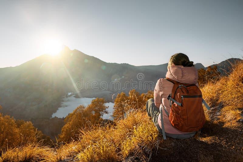 Junge Frau mit dem Wanderer, der Sonnenaufgangansicht am hohen mounta genießt lizenzfreies stockfoto
