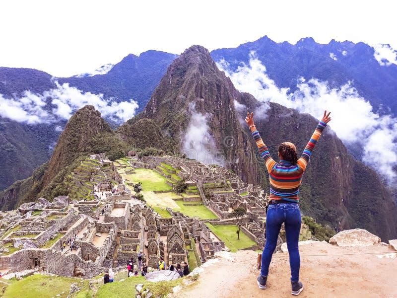 Junge Frau mit den angehobenen Armen auf Hintergrund von Machu Picchu lizenzfreies stockfoto