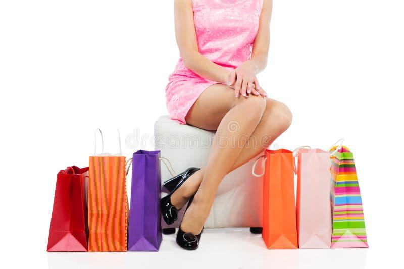 Junge Frau mit den dünnen Fahrwerkbeinen, die nahe bunten Einkaufstaschen sitzen stockfotos