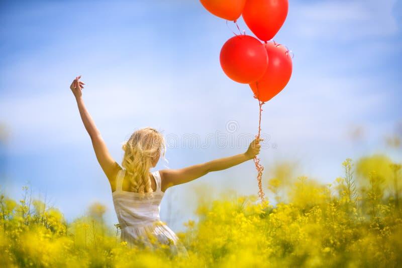 Junge Frau mit den Händen hob auf Frühlingsfeld von gelben Blumen an stockbild