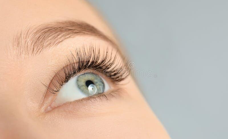 Junge Frau mit den schönen langen Wimpern auf grauem Hintergrund, Nahaufnahme stockbild