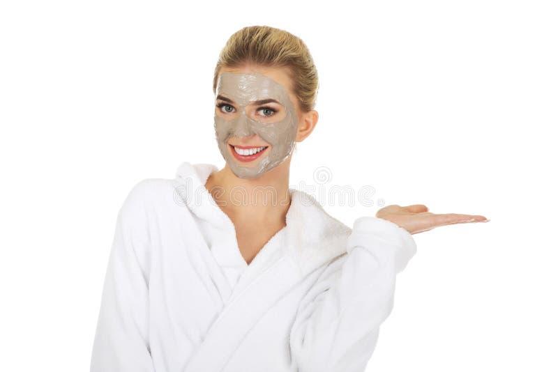 Junge Frau mit der Gesichtsmaske, die etwas auf ihrer Hand hält lizenzfreies stockbild