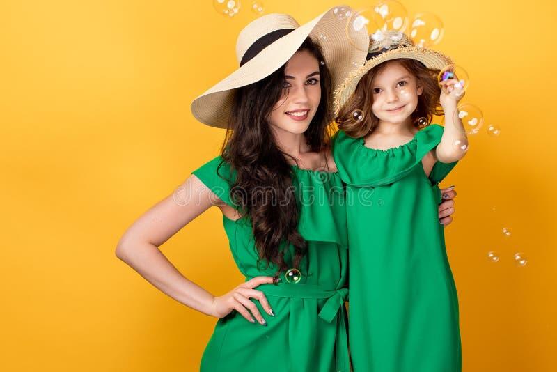 Junge Frau mit der Hand auf der Taille, die mit kleiner Tochter steht lizenzfreie stockbilder