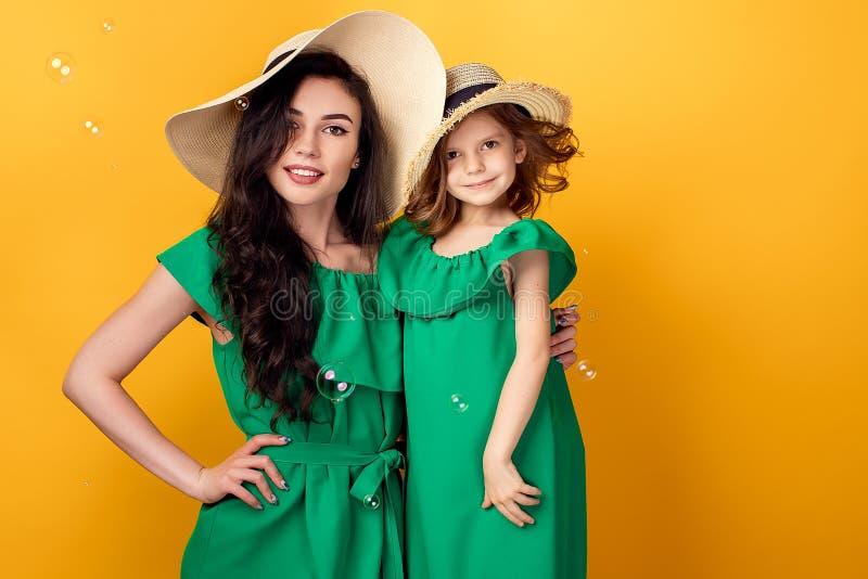 Junge Frau mit der Hand auf der Taille, die mit kleiner Tochter steht stockfotografie
