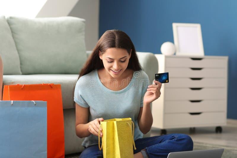 Junge Frau mit der Kreditkarte, die zu Hause Einkaufstasche untersucht stockbild