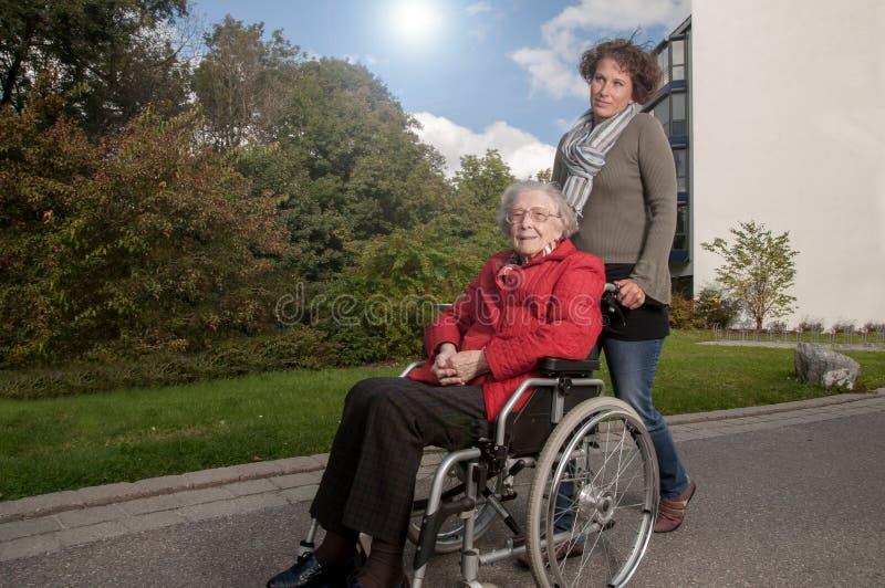 Junge Frau mit der ?lteren Frau, die im Rollstuhl sitzt lizenzfreie stockbilder