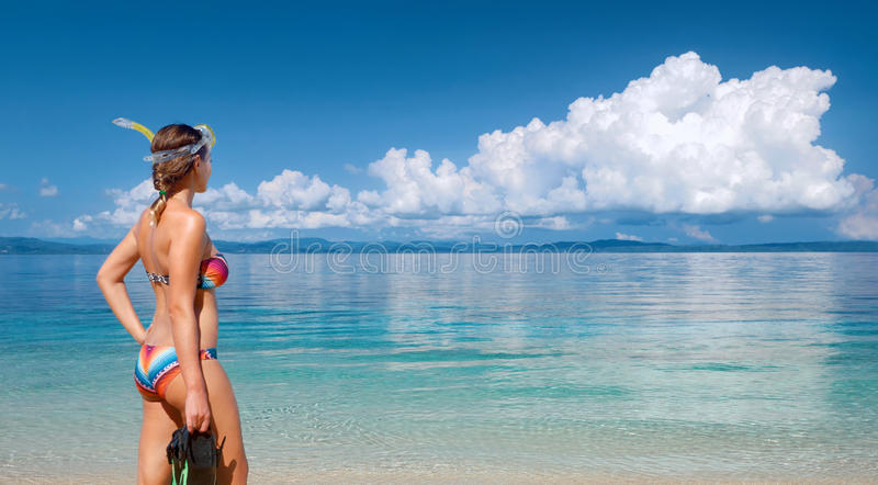 Junge Frau mit der Maske, die geht, im tropischen Strand zu schnorcheln stockfotografie