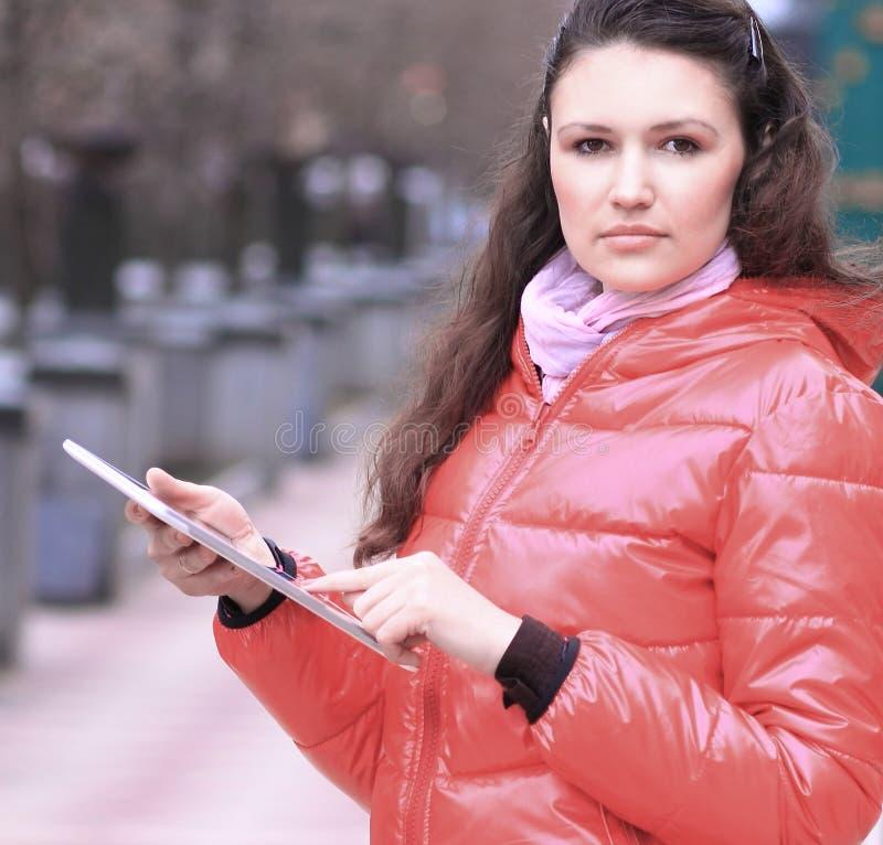 Junge Frau mit digitaler Tablette auf unscharfem Stadthintergrund stockfoto