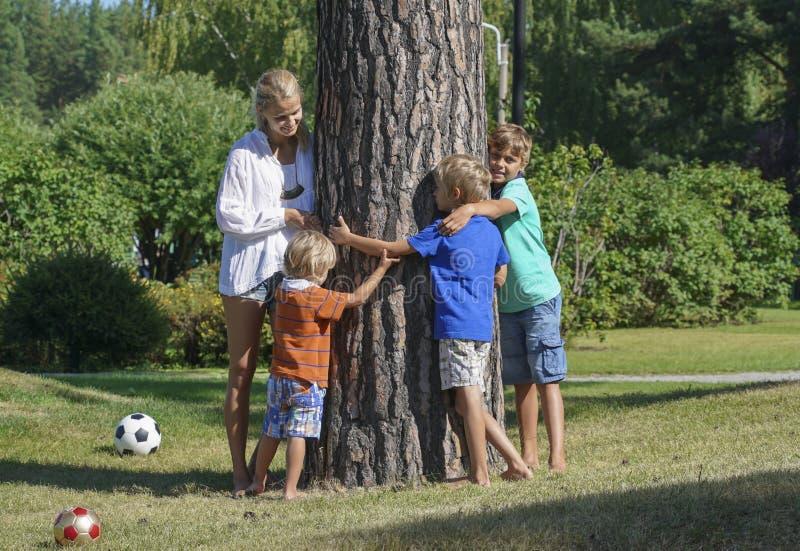 Junge Frau mit drei Kindern, die einen Baum umarmen lizenzfreie stockfotos