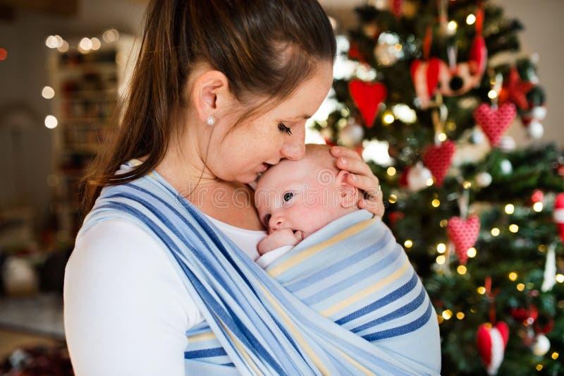 Junge Frau mit einem Baby zur Weihnachtszeit lizenzfreie stockbilder