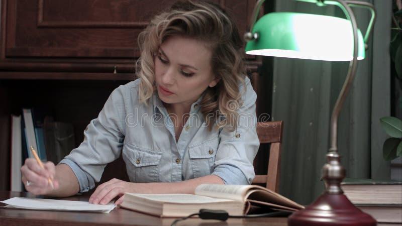 Junge Frau mit einem Buch setzt sich zum Tabelle hin, schaltet die grüne Lampe ein und fängt an zu arbeiten stockfoto