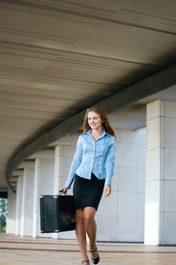Junge Frau mit einem großen Aktenkoffer lizenzfreies stockbild