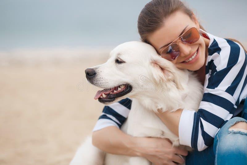 Junge Frau mit einem Hund auf einem einsamen Strand lizenzfreie stockbilder