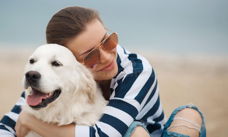 Junge Frau mit einem Hund auf einem einsamen Strand lizenzfreies stockbild