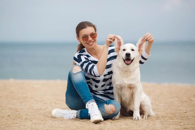 Junge Frau mit einem Hund auf einem einsamen Strand stockbild