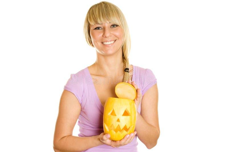 Junge Frau mit einem Kürbis für Halloween stockfotografie