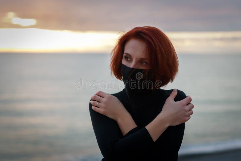 Junge Frau mit einem magischen Anstarren steht gegen den Sonnenunterganghimmel mit ihren gekreuzten Armen lizenzfreie stockfotos