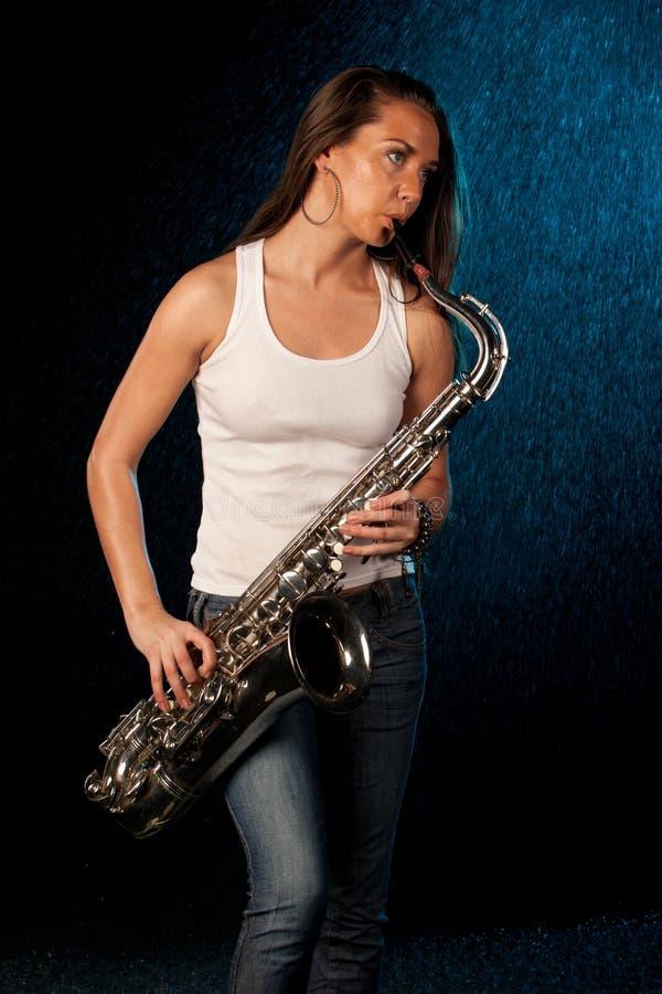 Junge Frau mit einem Saxophon stockbild