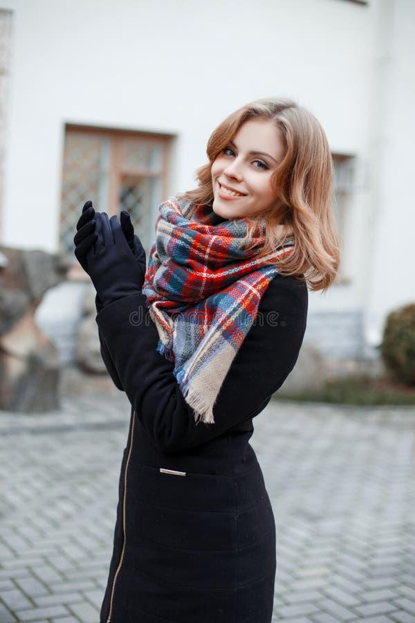 Junge Frau mit einem schönen Lächeln in einem Wintermantel in den schwarzen Handschuhen mit einem woolen modernen Schal, der drau stockfotos