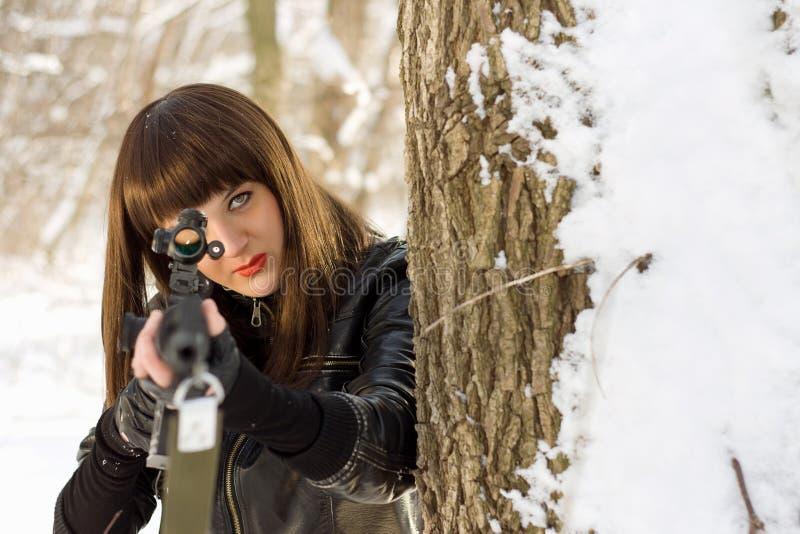 Junge Frau mit einem Scharfschützegewehr stockbilder