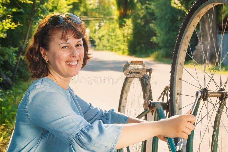 Junge Frau mit einem Schlüssel repariert ein Fahrrad auf einer Landstraße in der Landschaft in den Strahlen des Sonnenuntergangs stockbilder
