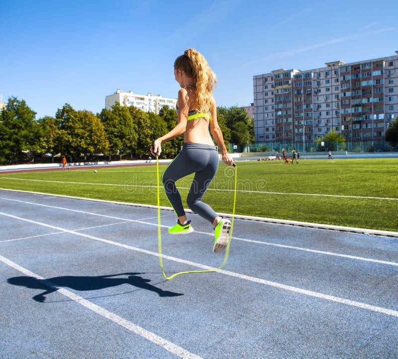 Junge Frau mit einem Springen fangen ihre Hände mit einem Stadion als b ein lizenzfreie stockbilder
