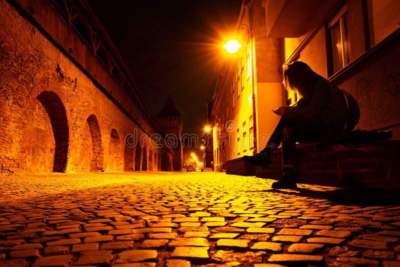 Junge Frau mit einem Telefon in der Hand, auf einer Bank, spät nachts, auf einer mittelalterlichen Artkopfsteinstraße in Sibiu, R lizenzfreie stockfotos