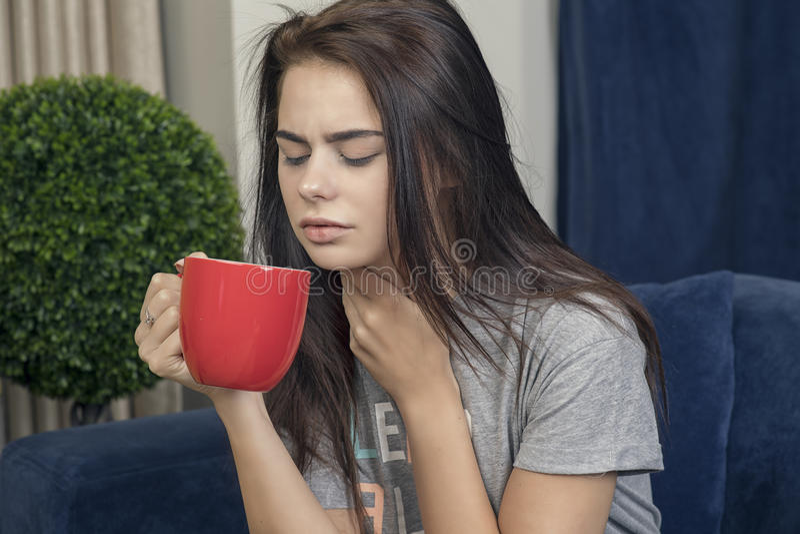 Junge Frau mit einem trinkenden Tee der Halsschmerzen lizenzfreies stockbild