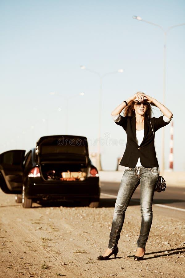 Junge Frau mit einem unterbrochenen Auto stockbilder