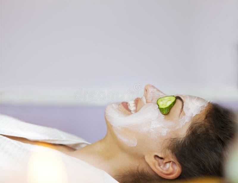 Junge Frau mit einer Gesichtsmaske und Gurke auf ihrem Gesicht lizenzfreie stockfotos