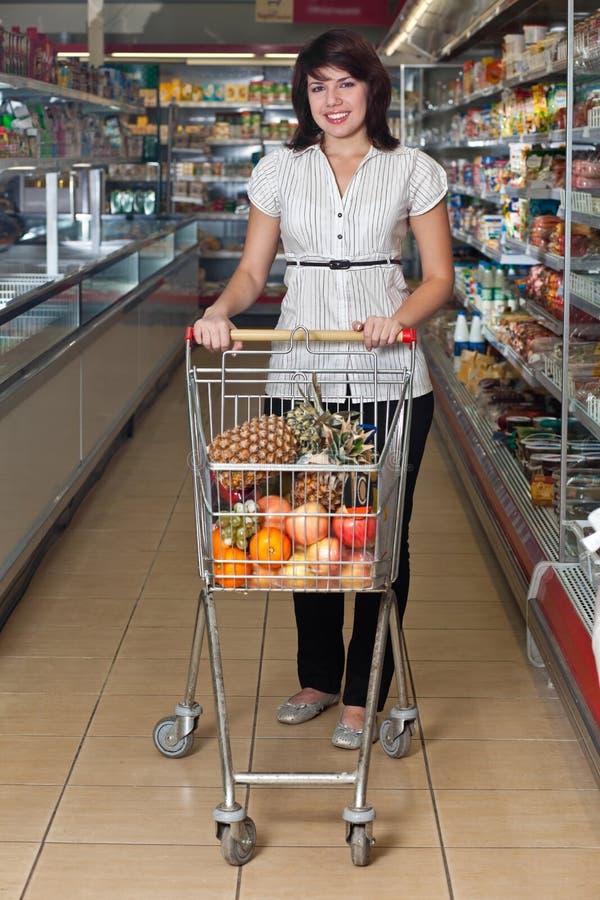 Junge Frau mit einer Laufkatze an einem Supermarkt lizenzfreies stockbild