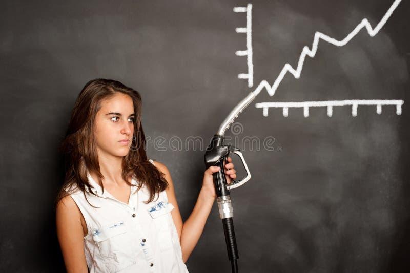 Junge Frau mit einer Tanksäuledüse stockbilder