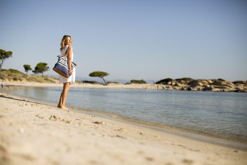 Junge Frau mit einer Tasche, die auf dem Strand steht stockfotos