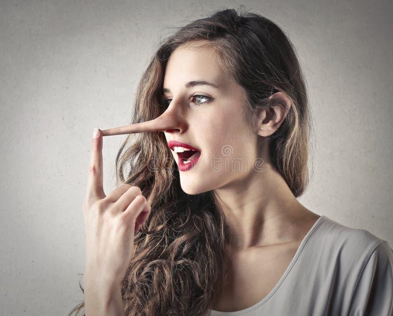 Junge Frau mit eines Pinocchios Nase lizenzfreie stockfotografie