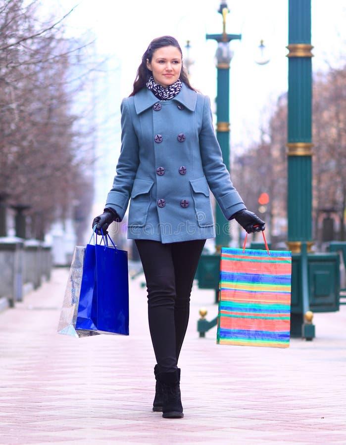 Junge Frau mit Einkaufstaschen gehend hinunter die Straße der Stadt lizenzfreie stockfotos