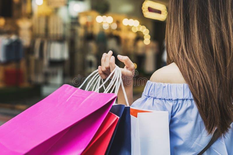 Junge Frau mit Einkaufstaschen im Shop stockfotos