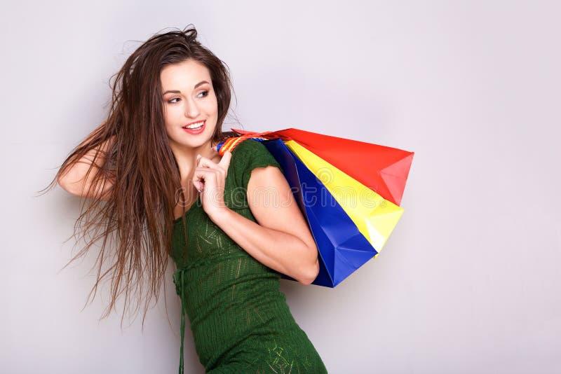 Junge Frau mit Einkaufstaschen und hinten schauen stockbilder