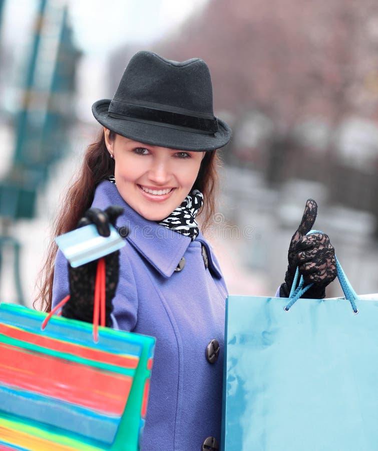 Junge Frau mit Einkaufstaschen und Kreditkarte auf dem Hintergrund der Stadt lizenzfreie stockbilder