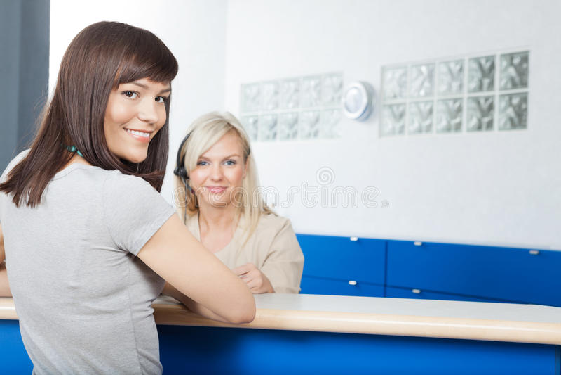 Junge Frau mit Empfangsdame At Dentists Büro lizenzfreie stockbilder