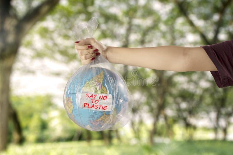 Junge Frau mit Erdkugel und Plastiktasche lizenzfreies stockfoto