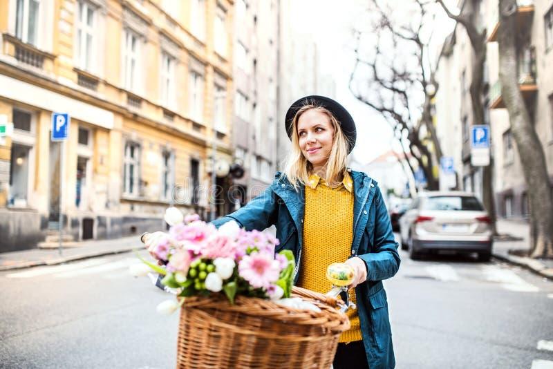 Junge Frau mit Fahrrad und Blumen in der sonnigen Frühlingsstadt stockbilder