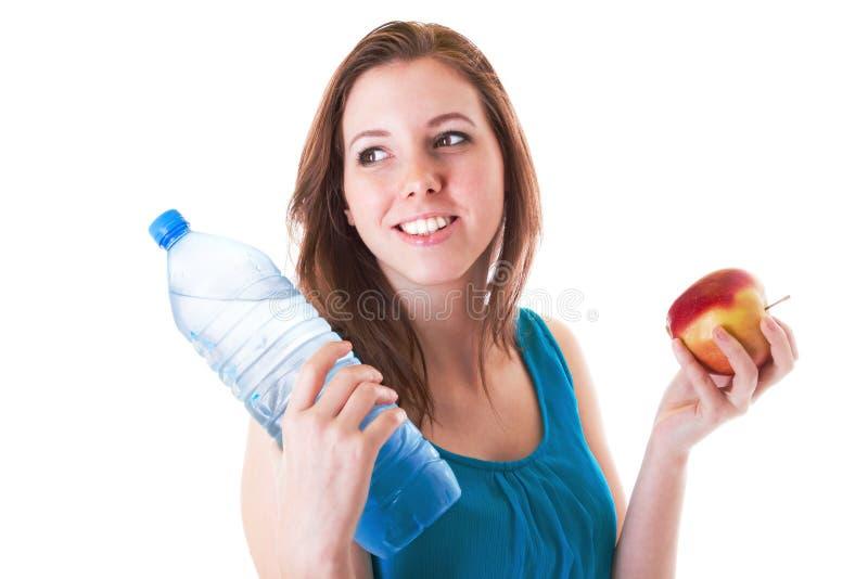 Junge Frau mit Flasche des Wassers und des Apfels stockfotos