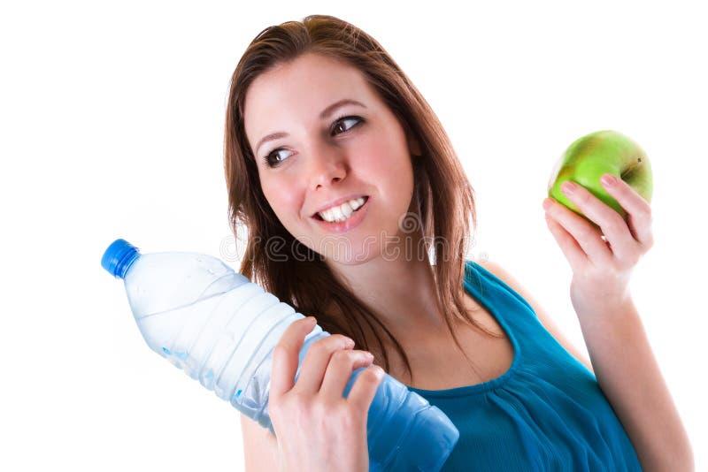 Junge Frau mit Flasche des Wassers und des Apfels lizenzfreies stockfoto