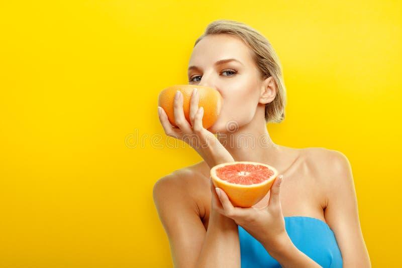 Junge Frau mit Früchten auf Leuchtorangehintergrund stockfoto