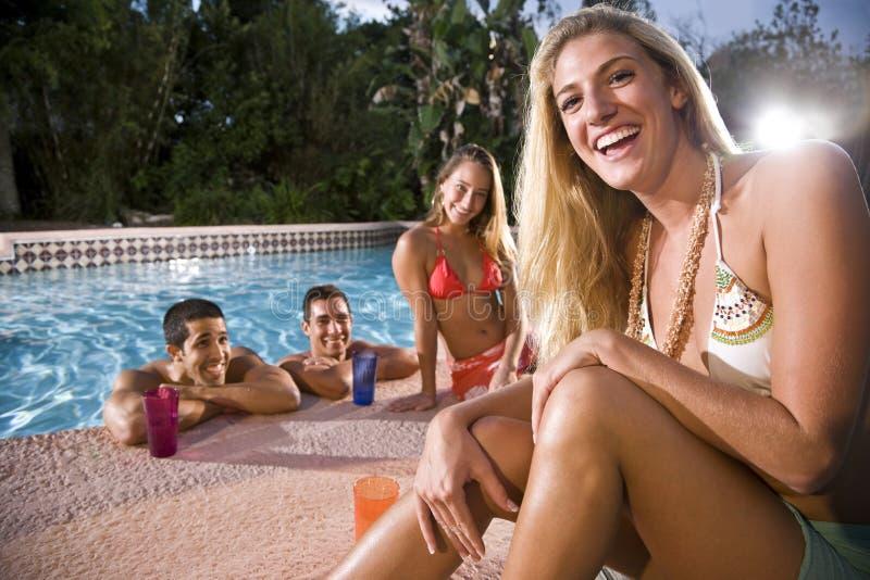 Junge Frau mit Freunden durch Swimmingpool stockbild