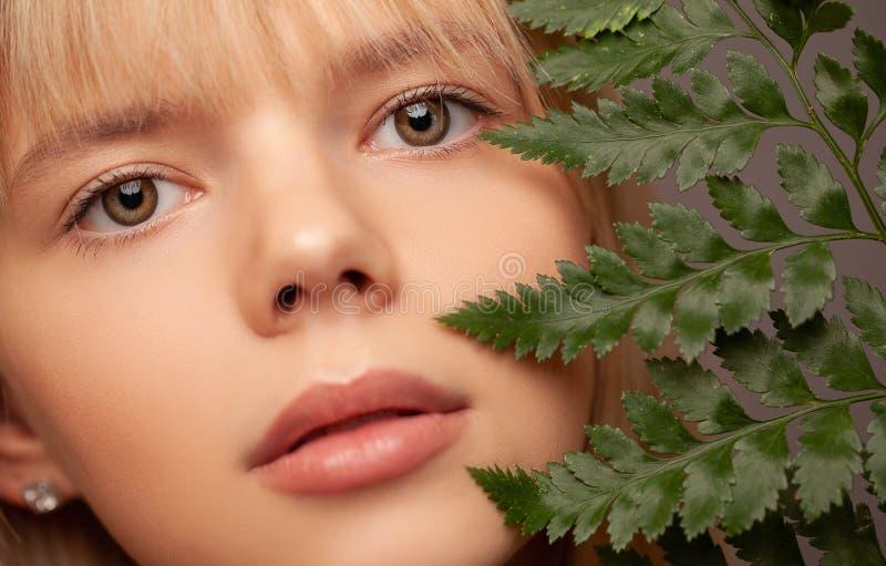 Junge Frau mit frischer gesunden Haut und den Haaren, die Farn und das Lächeln halten Cosmetology, Schönheit und Badekurort stockfotografie