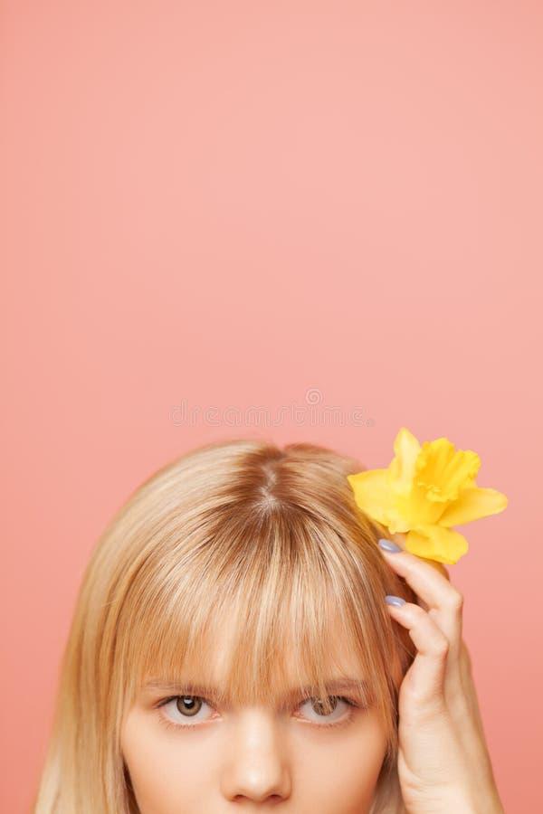 Junge Frau mit frischer gesunden Haut und den Haaren, die Narzissen und das Lächeln halten Cosmetology, Schönheit und Badekurort stockbild