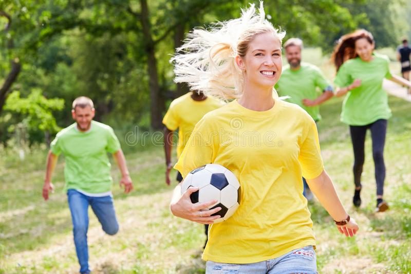 Junge Frau mit Fußball im Rennen lizenzfreies stockbild