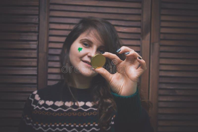 Junge Frau mit gemaltem grünem Klee auf ihrer Backe, die goldene Münze an der Stange vor einer hölzernen Wand hält stockbild